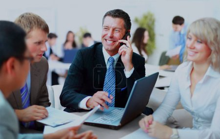 business man speaking on the phone while in a meeting .