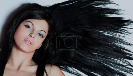 Portrait of pretty young smiling woman with straight long hair.