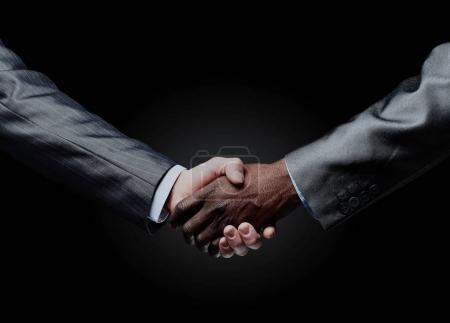 African businessmans hand shaking white businessmans hand.