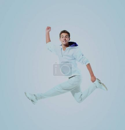 Jumping young man. Isolated over blue background.