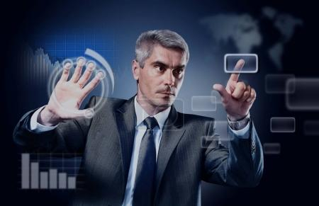 Businessman pressing high tech type of modern buttons on a virtual background.