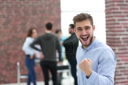 Handsome  businessman celebrating victory shouting happily in th