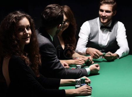 players sitting at the playing table in the casino