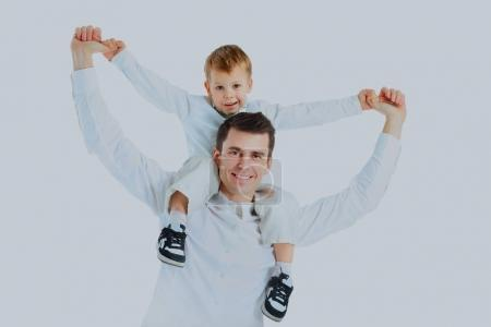 Dad holding his son on his shoulders, his arms outstretched.