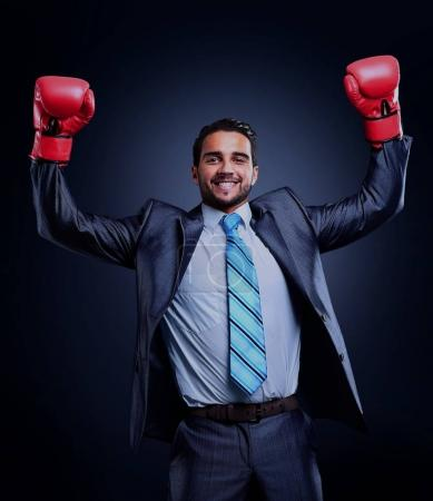 Businessman in a suit and boxing gloves, celebrating a win, isolated on black background.
