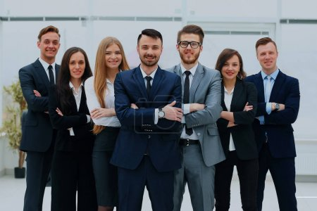 Smiling and confident business team standing in front of a bright window.