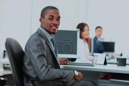 Portrait of a happy African American entrepreneur displaying computer laptop in office.