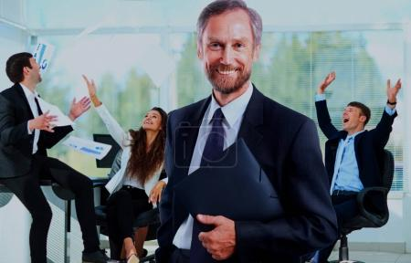 Happy businessman standing in front of his colleagues in office.