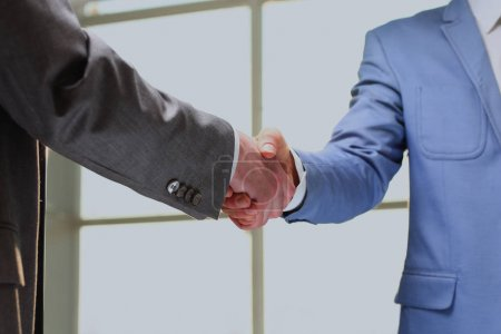 handshake of business partners after signing promising contract.