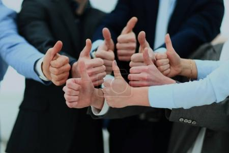 Close-up of business team holding their thumbs up.