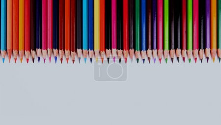 Assortment of coloured pencils with shadow on white background.