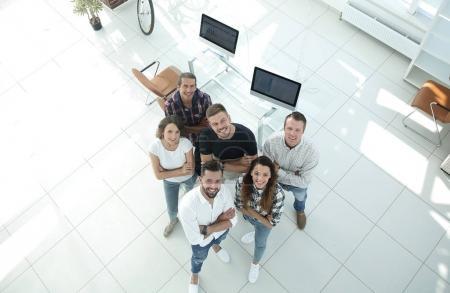 Foto de Ver la parte superior. un grupo de profesionales creativos de pie en la oficina y mirando hacia arriba - Imagen libre de derechos