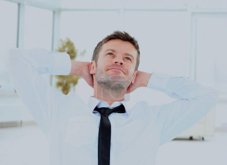 young businessman dreaming with his hands behind his head sitting in the office.