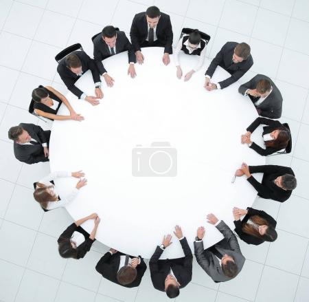 coach leads the session with business team sitting at a round table.