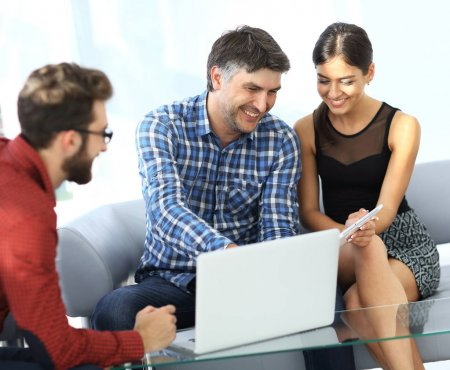 Business colleagues discussing on report with laptop on table