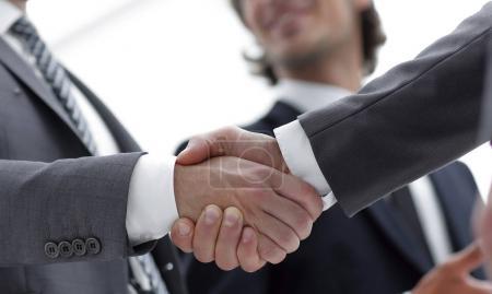Photo pour Hommes d'affaires confiants se serrant la main et le sourire lorsque vous vous trouvez au bureau ensemble - image libre de droit