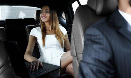 Photo pour Femme entrepreneur travaillant pendant un voyage au bureau dans une voiture de luxe. - image libre de droit