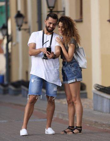Photo pour Couple de touristes marchant en ville et regardant leurs photos - image libre de droit