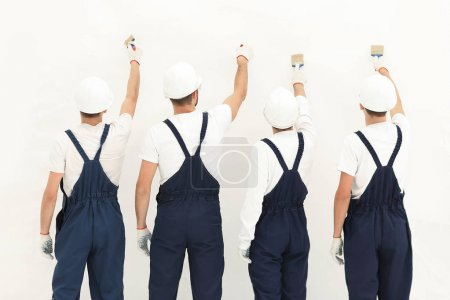 Photo for Rear view.team of construction workers paint a wall.photo with copy space. - Royalty Free Image