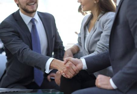 Two colleagues handshaking after meeting.