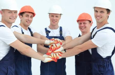 team of builders standing with hands clasped together