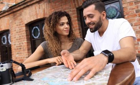 Photo pour Couple dans un café en plein air en utilisant la carte et l'itinéraire de planification - image libre de droit