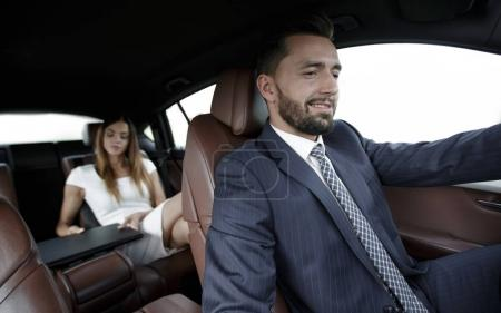 businessmen with a computer in the car go on a business trip