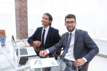 two business person sitting behind a Desk