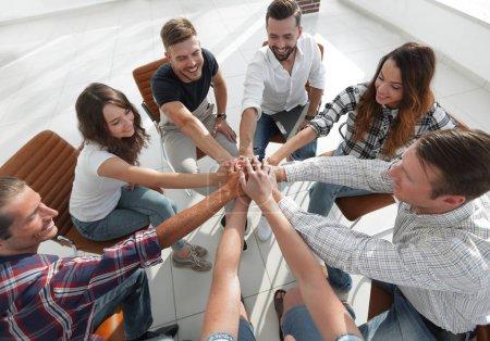 Photo pour Équipe entreprise prospère, assis au milieu du bureau et les mains jointes ensemble - image libre de droit