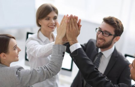 Photo for Successful business team giving each other a high-five, standing in the office.concept of success. - Royalty Free Image