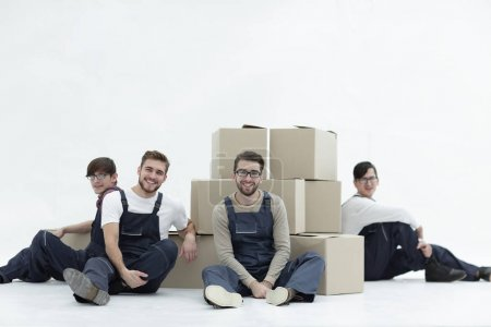 Photo for Satisfied and proud movers leaning on stack of boxes isolated on white background, - Royalty Free Image