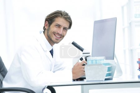 Male Chemist Scientific Reseacher using Microscope in Laboratory
