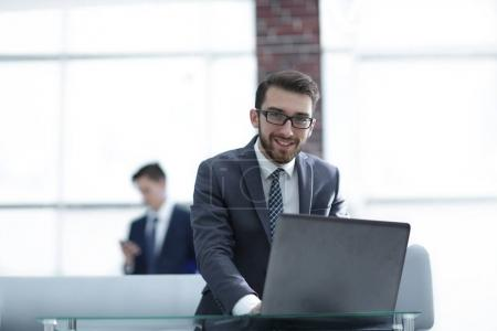 Handsome businessman is working with laptop in office