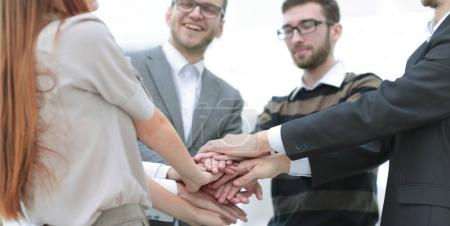 Business team standing joining hands together