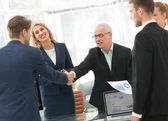 Businessmen shaking hands in conference room in office
