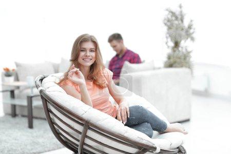 Photo pour Jeune femme assise dans une grande chaise confortable dans le fond flou du salon - image libre de droit