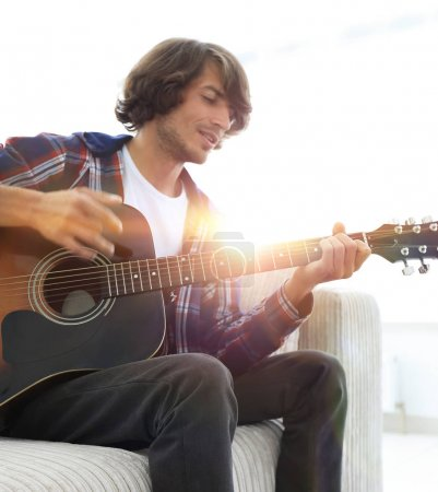 guy sings a song and plays guitar sitting on the couch.