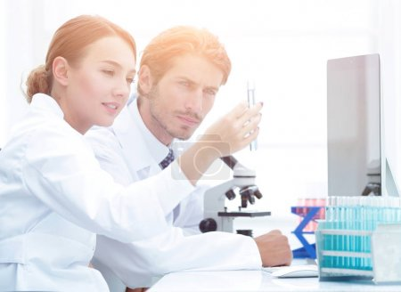 Woman looking at test tubes with colorful liquids
