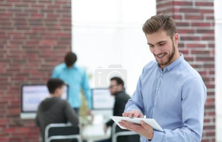 Photo pour Beau homme d'affaires utilisant une tablette dans le bureau . - image libre de droit