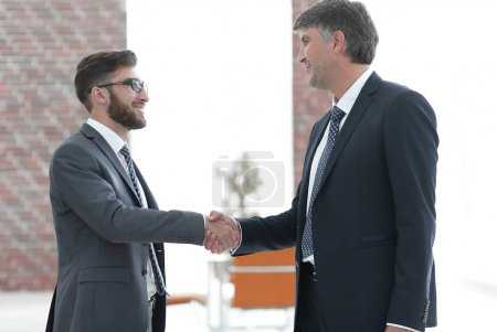 Photo pour Deux souriant succès jeunes entrepreneurs secouant les mains sur la réunion d'affaires au bureau - image libre de droit
