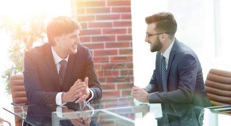 Foto de Dos hombres de negocios discuten tareas sentados en una mesa. Concepto empresarial - Imagen libre de derechos