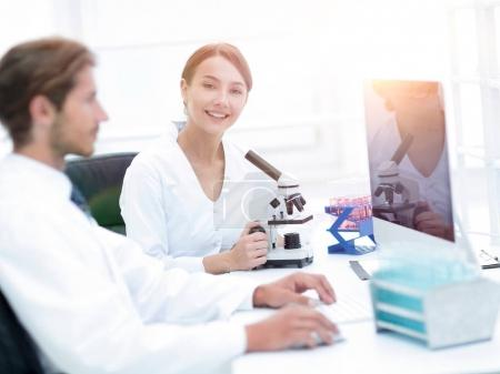 Lab expert working on a test using microscope