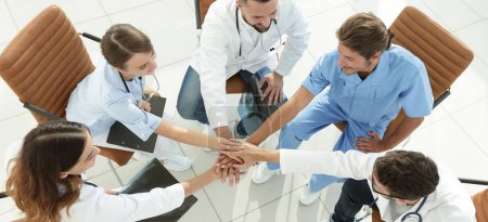 medical staff hands clasped together,sitting at a Desk