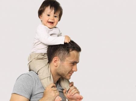 the little boy is sitting on the shoulders of Dad