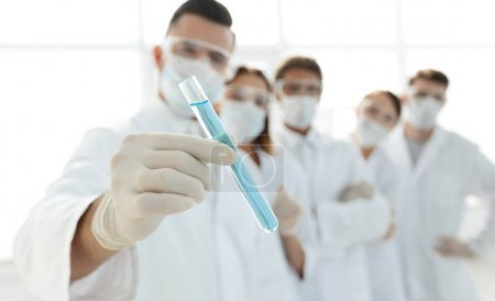 background image is a group of medical workers working with liquids in laboratory