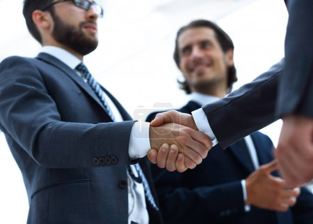 Photo for Confident businessmen shaking hands and smiling while standing at office together - Royalty Free Image