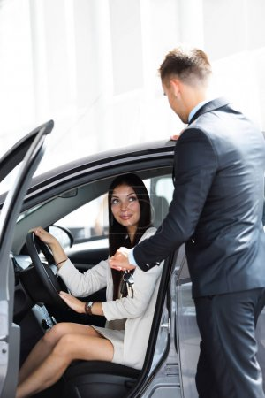 young woman gets the key and smiling, sitting in a new car in the showroom.