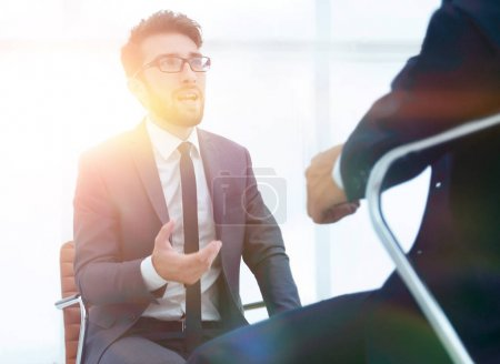 man sitting on chair in office listening to business businessman