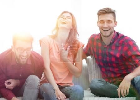 Photo pour Groupe de jeunes gens riant et assis sur le canapé. photo avec espace de copie - image libre de droit