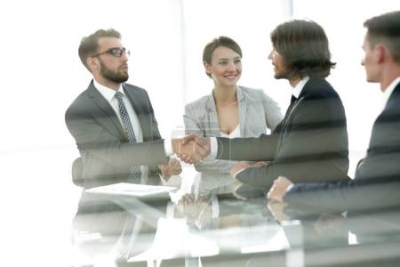 from behind the glass.handshake of business partners